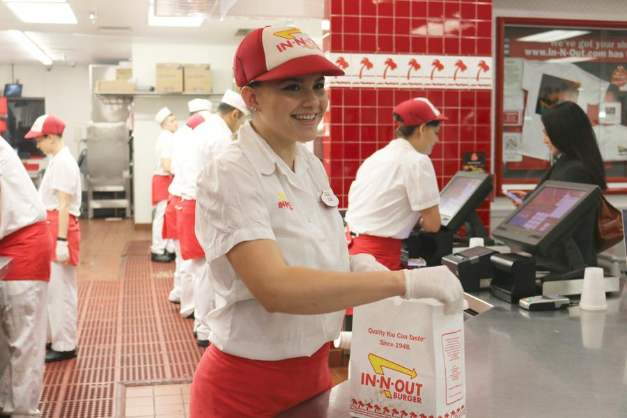 (TARAH JOHNSON/EYE OF THE TIGER) Leah Yaranon works the counter at In-N-Out Burger while her siblings flip burgers in the kitchen.
