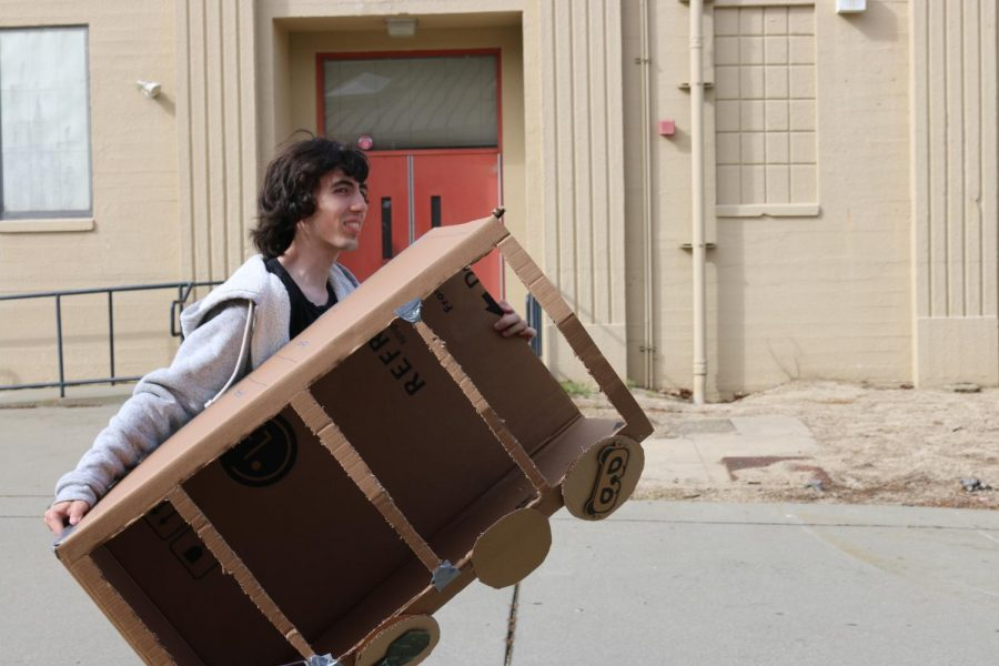 Junior+Ike+Bischof+carries+in+a+cardboard+box+to+use+in+his+self-written+musical.+